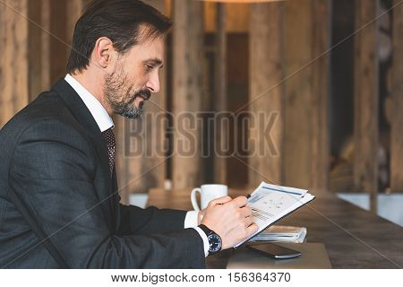 Confident middle-aged man is reading document with concentration. He is sitting at table in cafe
