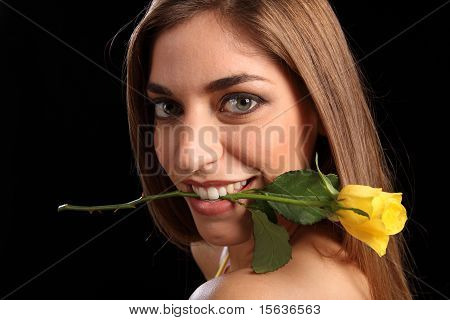 Woman holding yellow rose in her mouth
