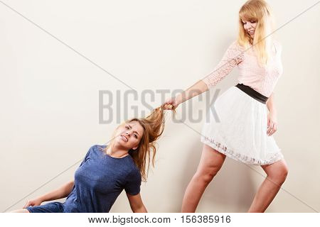 Aggressive mad women fighting each other pulling hair. Two young girls struggling win catfight. Violence.