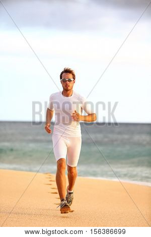 Athlete runner training cardio on beach race living an active and healthy lifestyle. Professional triathlete working out exercising body full length on sand during summer sunset. Competition workout.