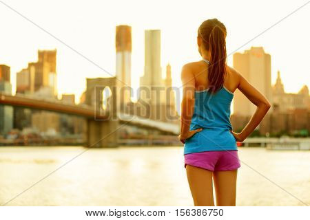 New York city lifestyle active people living an urban active life. Fitness healthy woman runner relaxing after running outdoors enjoying view of Brooklyn Bridge.