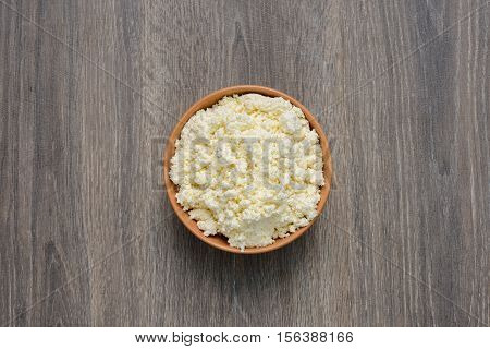 Cottage cheese or curd in deep dish on wooden table