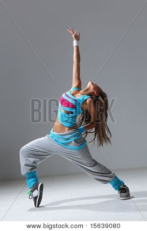 hip-hop style dancer posing on studio background