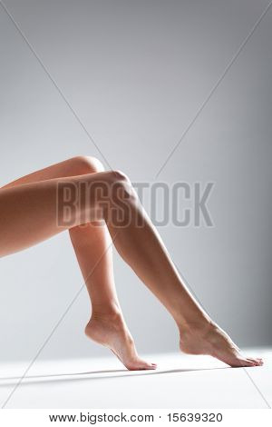 Smooth female legs on a grey background