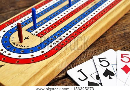 A top view image of a red, white, and blue cribbage board with the red cribbage peg in the winning position.