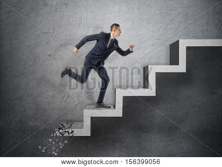 A businessman running up a concrete staircase, which is crushing down after him on the background of a grey wall. Business and management. Running away from the problems. Taking risks.