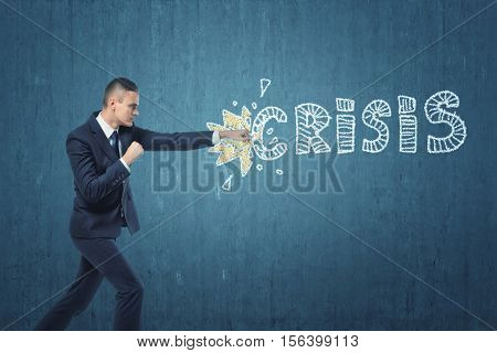A businessman punching hard the word 'crisis' written on the dark blue wall. Issues in business management and economics. Resolving the problems. Difficulties related to industry and enterprise.