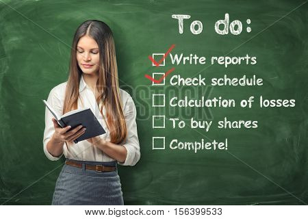 A young woman holding her day planner standing near the list of things to do at work written on the green chalkboard. Daily routine and time-management. Check schedule and write reports. To allocate resources appropriately.