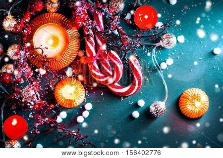 Christmas Holiday Background with Candy Cane, decorations, candles, garland and evergreens border over dark background table. Christmas and New year food. Christmas dinner, served table, decorations