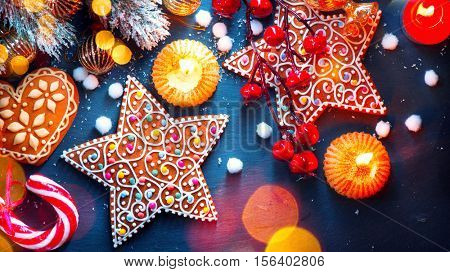 Christmas Holiday Background with ornate Gingerbread cookies, Candy Cane and evergreens border over black background table. Christmas and New year food. Christmas decoration