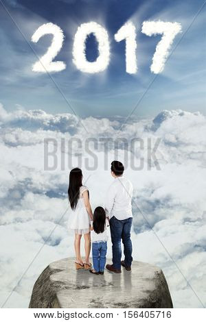 Image of happy family looking on the sky with number 2017 while standing on the stone and holding hands with each other