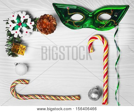 On white background wooden Christmas concept. Branch fir tree New year gift candy cane Christmas balls gold fir-cone Christmas snowflake marzipan. Christmas mask. Christmas card.Top view blank space