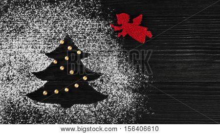 Christmas card. On dark wooden background Christmas tree made of icing sugar flour. Red Christmas angel flies to New Year tree. Top view blank space