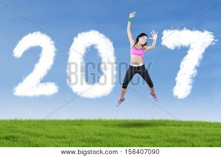 Indian athlete jumping on the meadow while forming number 2017 in the blue sky