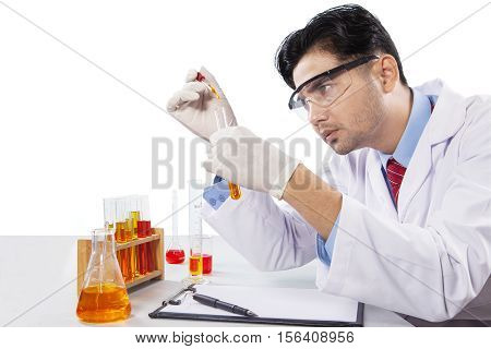 Portrait of male scientist makes chemical research by using chemical liquid isolated on white background