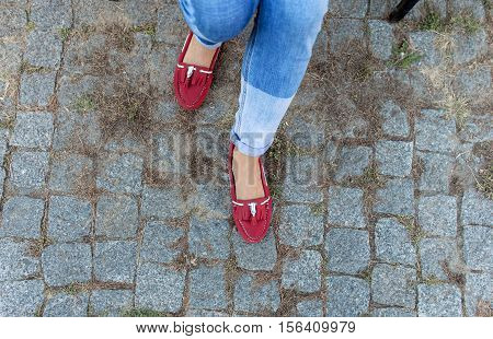 Womens foot close up in jeans and red loafers. Copy space