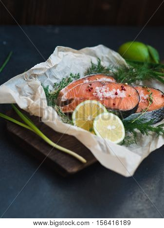 Fresh raw salmon steak on wooden cutting board with salt, garlic, lime and herbs