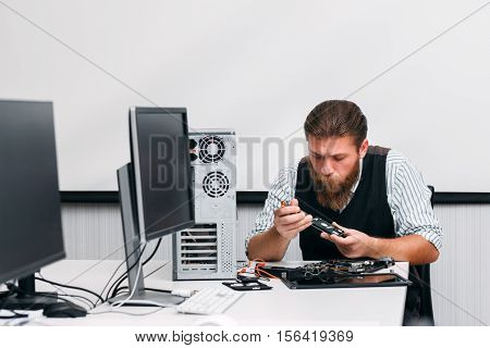 Engineer disassembling dvd drive part of CPU. Cd rom renovation in repair shop. Electronic renovation, business, technology concept