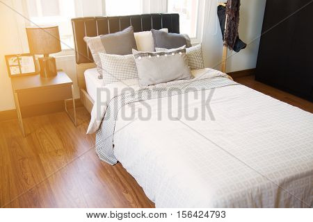 Modern bedroom interior with warm light from the sun. Relax day in bedroom on free day. Feeling relax and feeling enjoy on the bed in modern bedroom. modern interior and furniture in home.