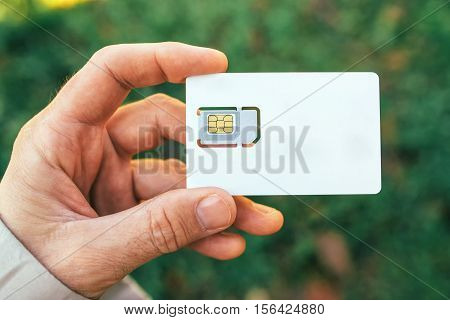 Male hand holding blank mobile phone gsm SIM card outdoors