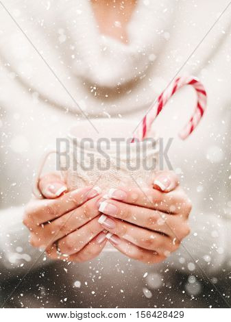 Woman holds a winter cup close up. Woman hands with elegant french manicure nails design holding a cozy knitted mug with cocoa, tea or coffee and a candy cane. Winter and Christmas time concept.