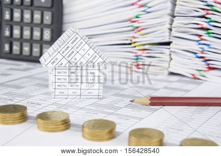 House And Pencil Have Blur Pile Gold Coins As Foreground