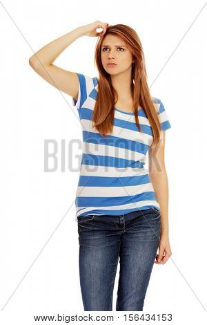 Pensive teenage woman scratching her head
