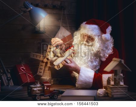 Merry Christmas and Happy Holidays! Santa Clause is preparing gifts for children for Xmas at his desk at home. Christmas legends and traditions.