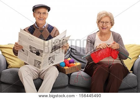 Mature man holding a newspaper and a mature woman knitting sitting on a sofa isolated on white background