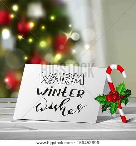 Christmas Greeting Card with nadwritten Warm Winter Wishes letters Vector on blured Christmas tree background