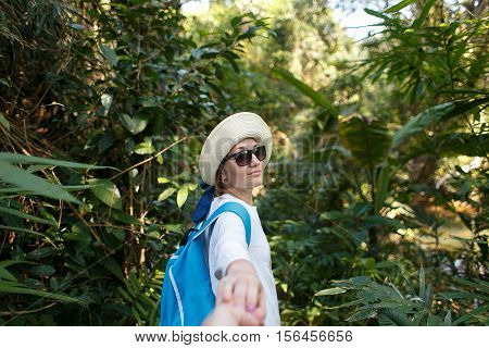 Follow me. Travel concept. Back view of young woman with backpack outdoors discovering jungle holding boyfriend's hand.
