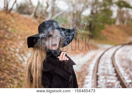 Young woman in a black dress and hat smoking a cigarette waiting for a train. The concept of loneliness and expectations. Travel alone.