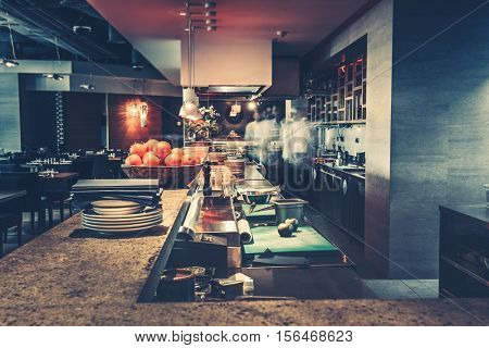 Restaurant kitchen interior: bar counter made of natural stone, fences off the open kitchen and hall for visitors with tables and chairs. In the background buzzing restaurant work motion chefs
