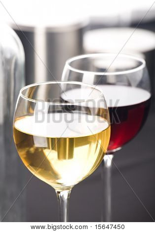 Two glasses of white and red whine.  Grey background