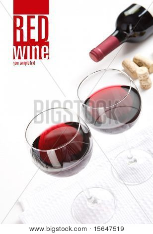Winery menu project. Two glasses of red wine, corks & bottle of wine on white table cloth. Space for text isolated on white.
