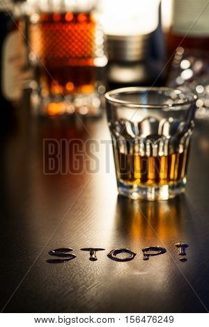 The word Stop on a bar with glass of alcohol in background