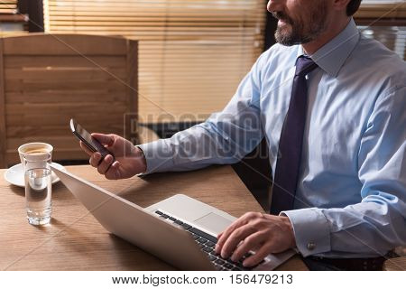 Useful electronic device. Nice handsome bearded man holding a cell phone and looking at its screen while sitting at the table