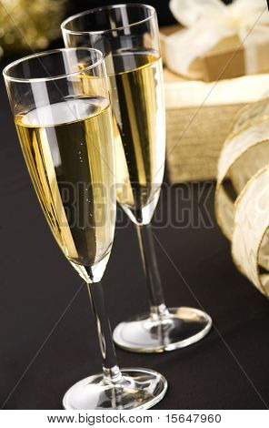 Two champagne flutes, elegant gold gifts boxes with white ribbon. All on matt black.
