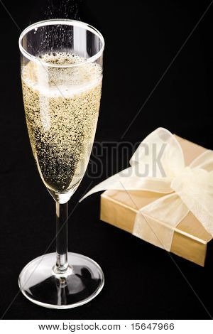 Champagne flute, elegant gold gift box with white ribbon. All on matt black.