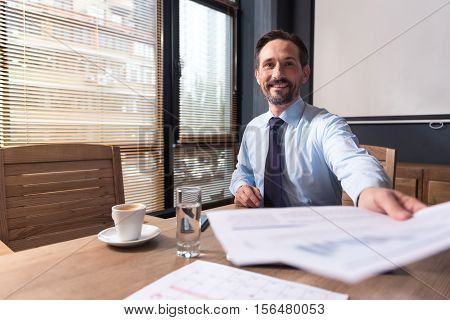 Work reports. Nice cheerful responsible manager sitting at the table and putting out his hand while giving you the documents