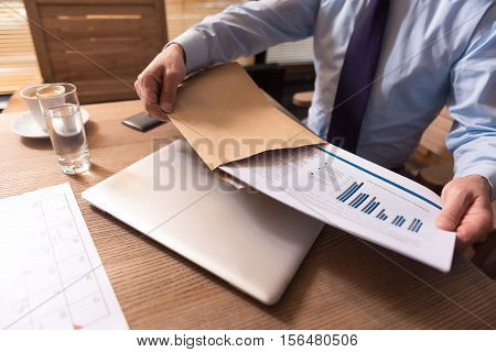 Business affairs. Close up of business documents with graphics and statistical data being taken out of the envelope by a hard working responsible male manager