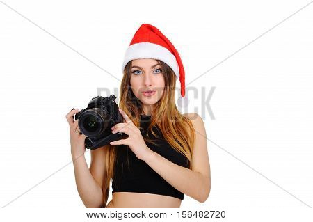 attractive young girl with the camera in a red Christmas hat on a white background. Christmas sale. Woman photographer in hat of Santa Claus. Christmas Pictures