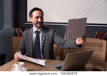 Preparing a presentation. Nice happy confident man holding a sheet of paper and looking at it while preparing to the presentation