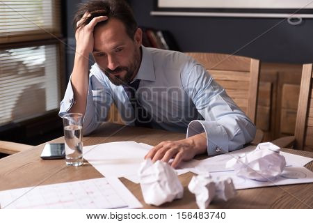Tight deadline. Handsome tired cheerless man sitting at the table and holding his head while having a tight deadline