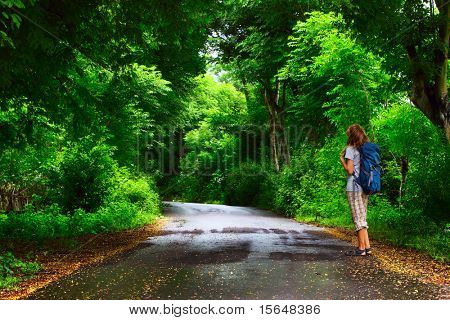Young woman with backpack standing on a wet asphalt path in a park and looking to a trees
