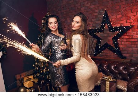 Two happy girls with a  a fireworks on their hands dancing, fun and waiting for Christmas time. Best wishes for a pleasant and successful New Year!