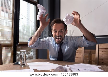 Nervous breakdown. Hysterical frantic angry man throwing crumpled paper around and grimacing while threatening you