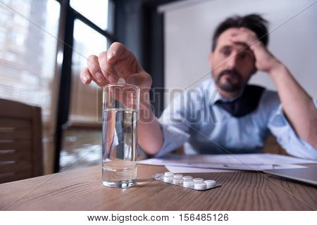Feeling ill. Exhausted gloomy pessimistic man holding his head and putting a pill into the glass of water while taking medicine