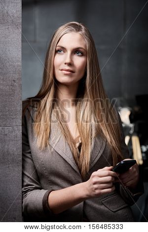 Portrait of attractive blonde businesswoman leaning against wall, holding mobile, looking away.