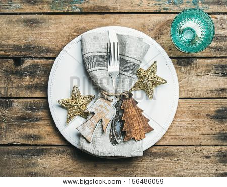 Christmas or New Year holiday table setting. White plate with linen napkin, napkin holders, silverware and golden stars, blue wine glass over wooden background. Party or family celebration concept